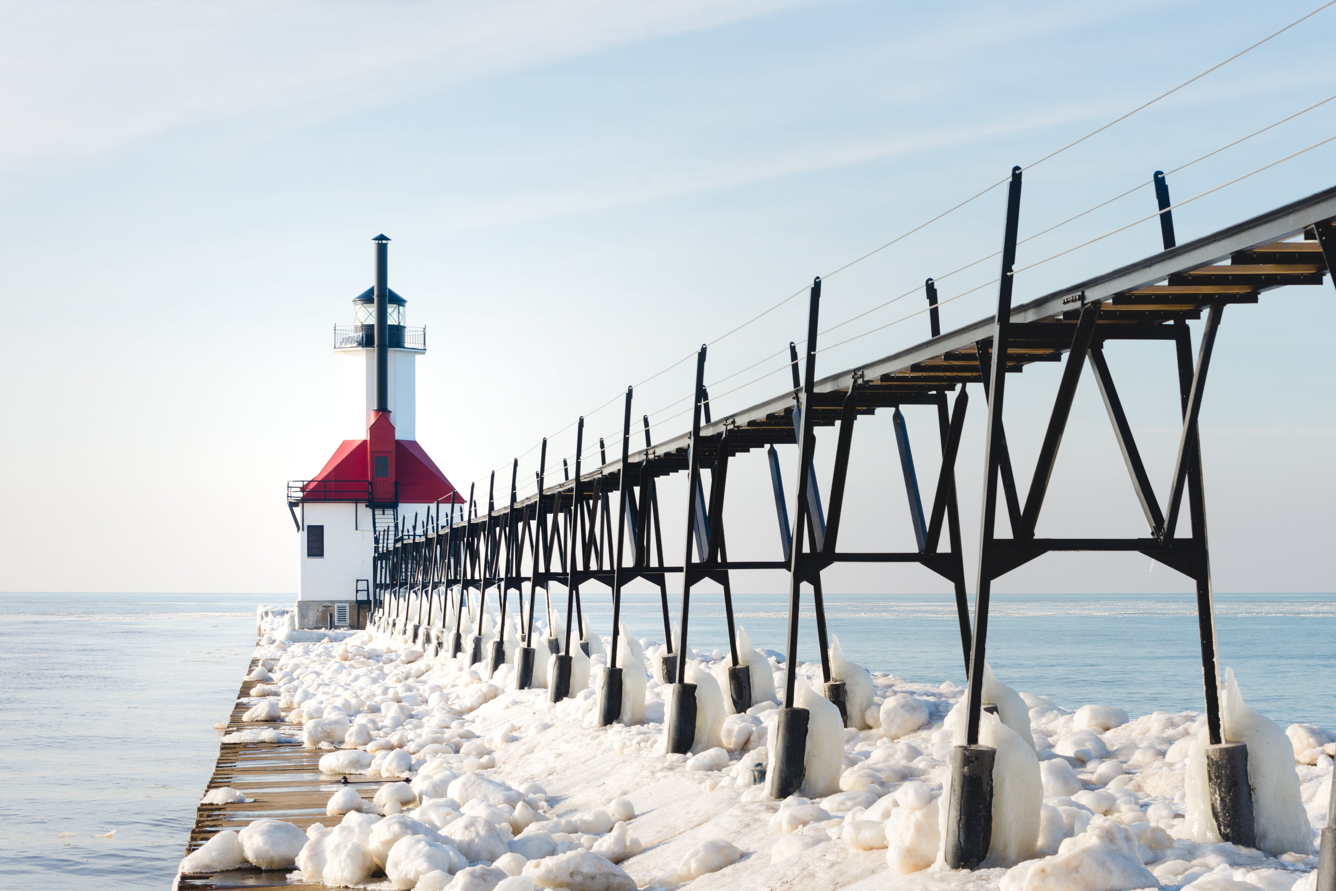 Red and White Concrete Lighthouse Surrounded by Snow Near Body of Water