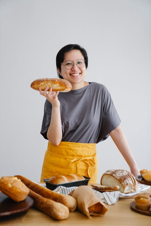 Man in Grey Crew Neck T-shirt and Yellow Shorts Holding Bread