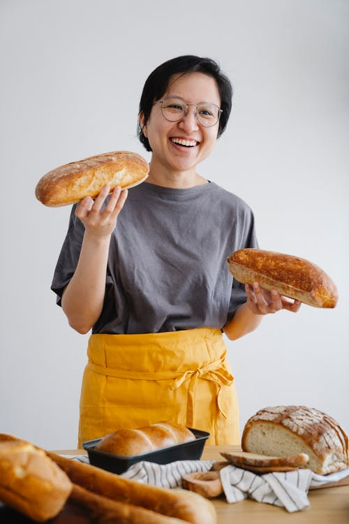 Man in Gray Crew Neck T-shirt Holding Bread