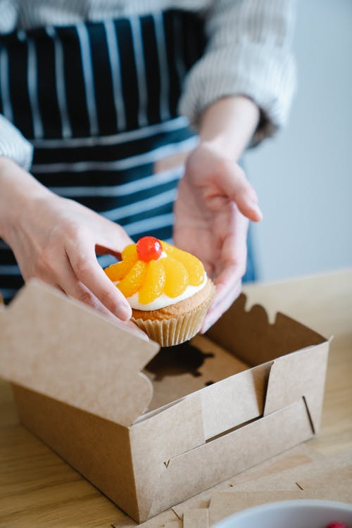 Person Holding Cupcake With Yellow Icing