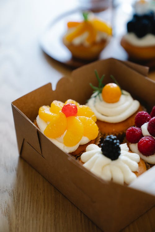 White and Brown Cupcakes With Berries on Brown Cardboard Box