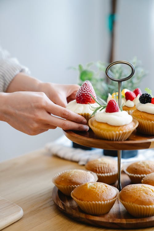 Person Holding Brown Wooden Tray With Cupcakes