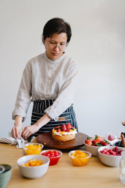 Woman in White Sweater Slicing Orange Fruit