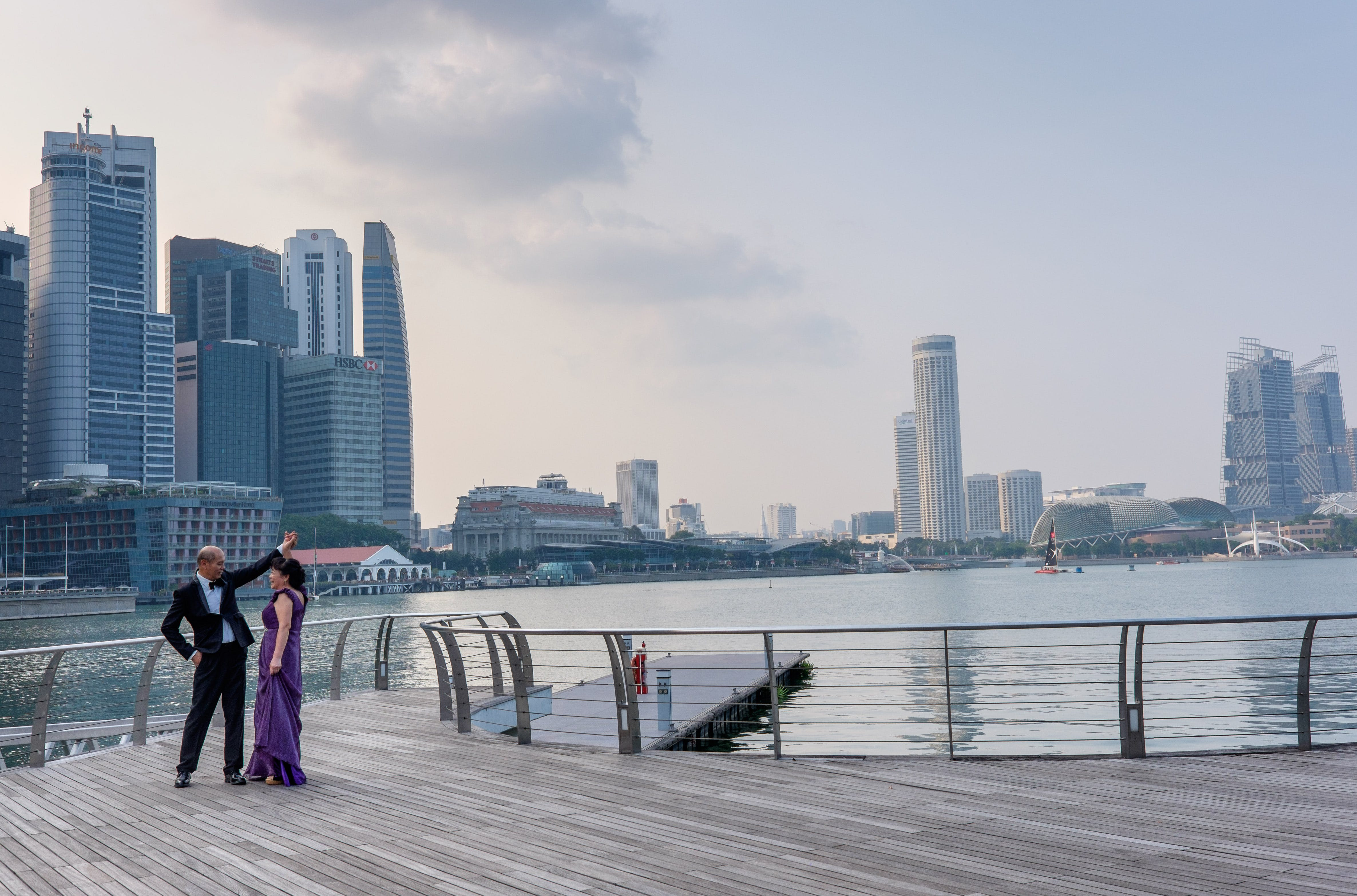 Man and Woman Dancing Beside Body of Water Under White Sky