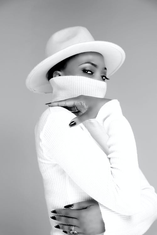 Black and white of serious African American female covering half face with collar of sweater wearing stylish headwear while looking at camera on gray background