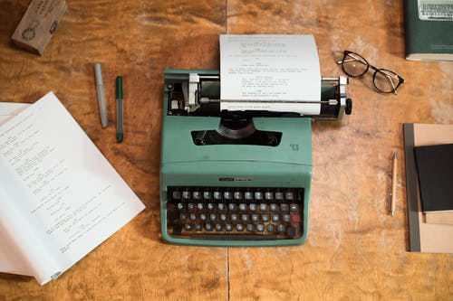 Green and Black Typewriter on Brown Wooden Table