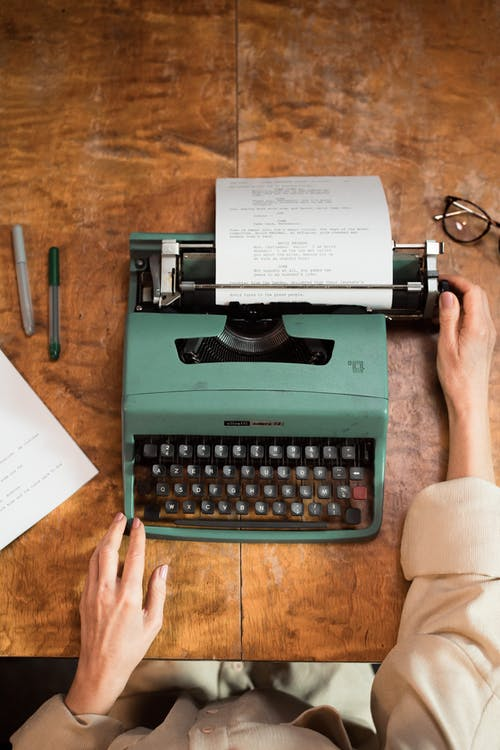Person Holding Green Typewriter on Brown Wooden Table
