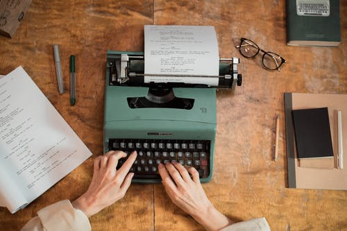 Person Typing on Green Typewriter on Brown Wooden Table