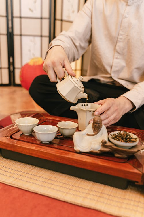 Person Pouring Liquid on Ceramic Teacup