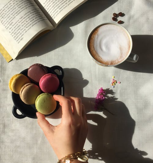 Close-Up Shot of a Person Holding a Macaroon beside a Cup of Cappuccino and an Open Book