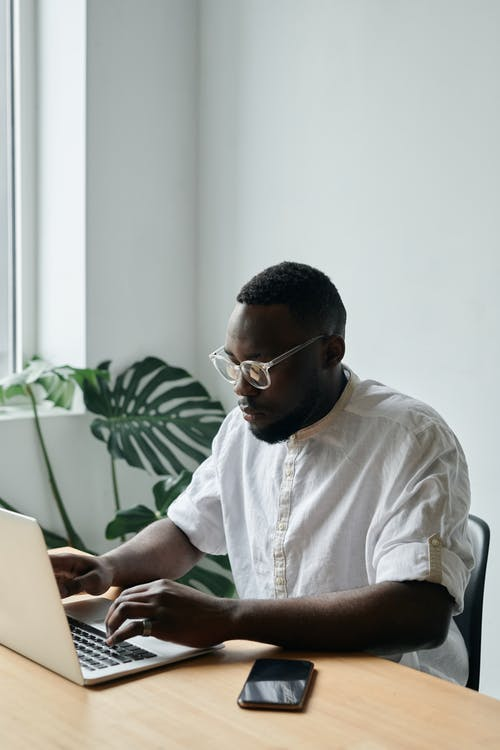 Photo of a Man in a White Shirt Typing on His Silver Laptop