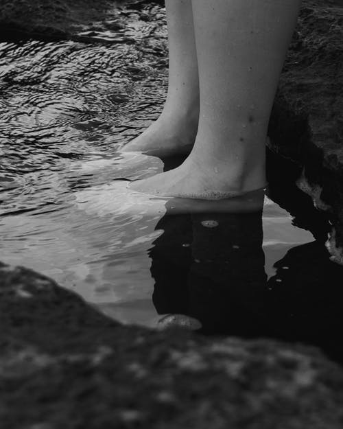 Grayscale Photo of Persons Leg on Water