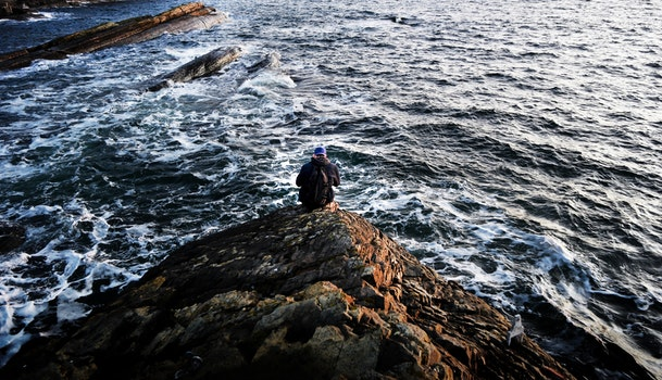 Photography of Person Sitting on Rock Near Ocean