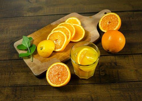 Close-Up Photo of Slices of Orange Near a Glass with Orange Juice
