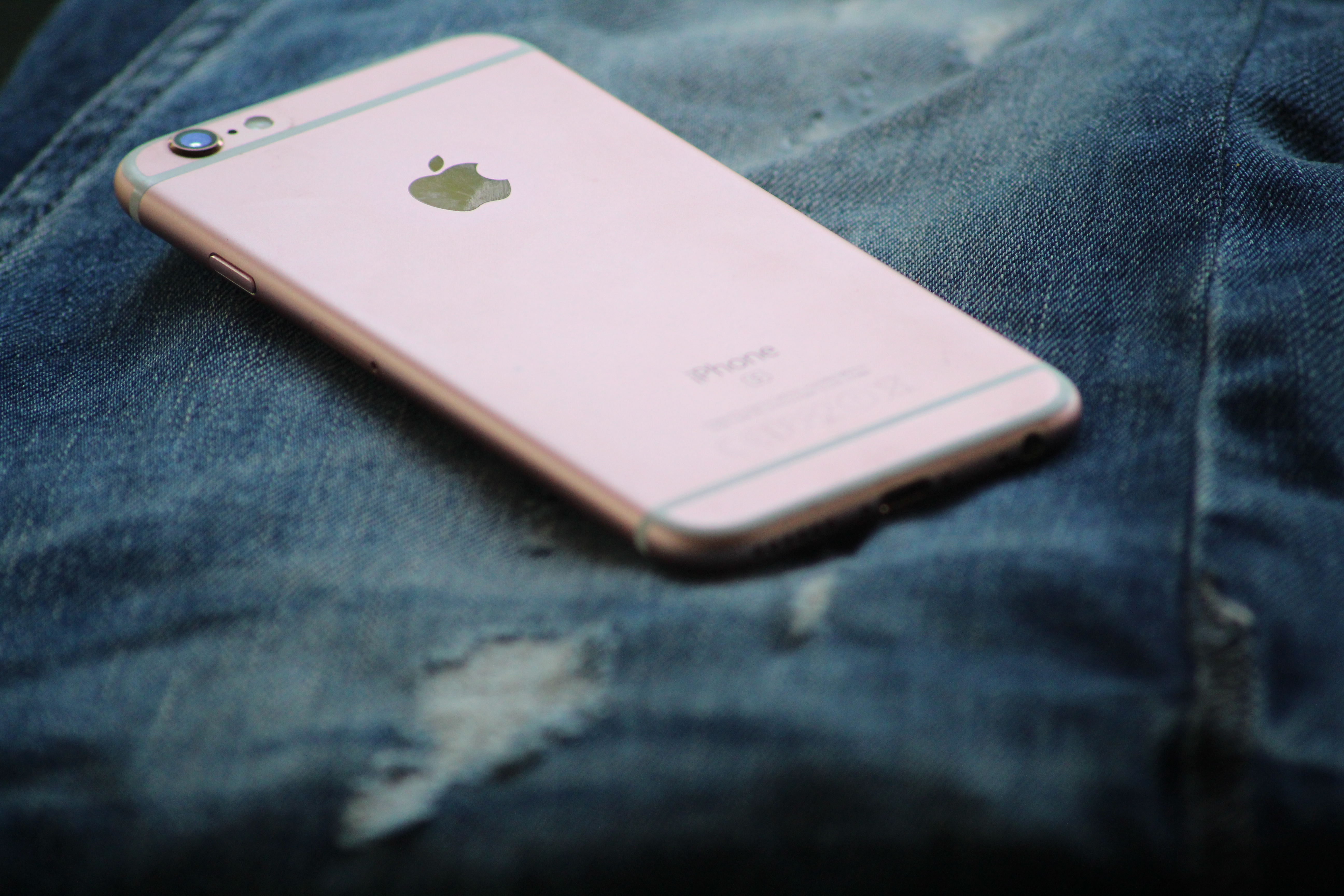 Close-Up Photography of Rose Gold Iphone 6s on Top of Blue Denim Jeans