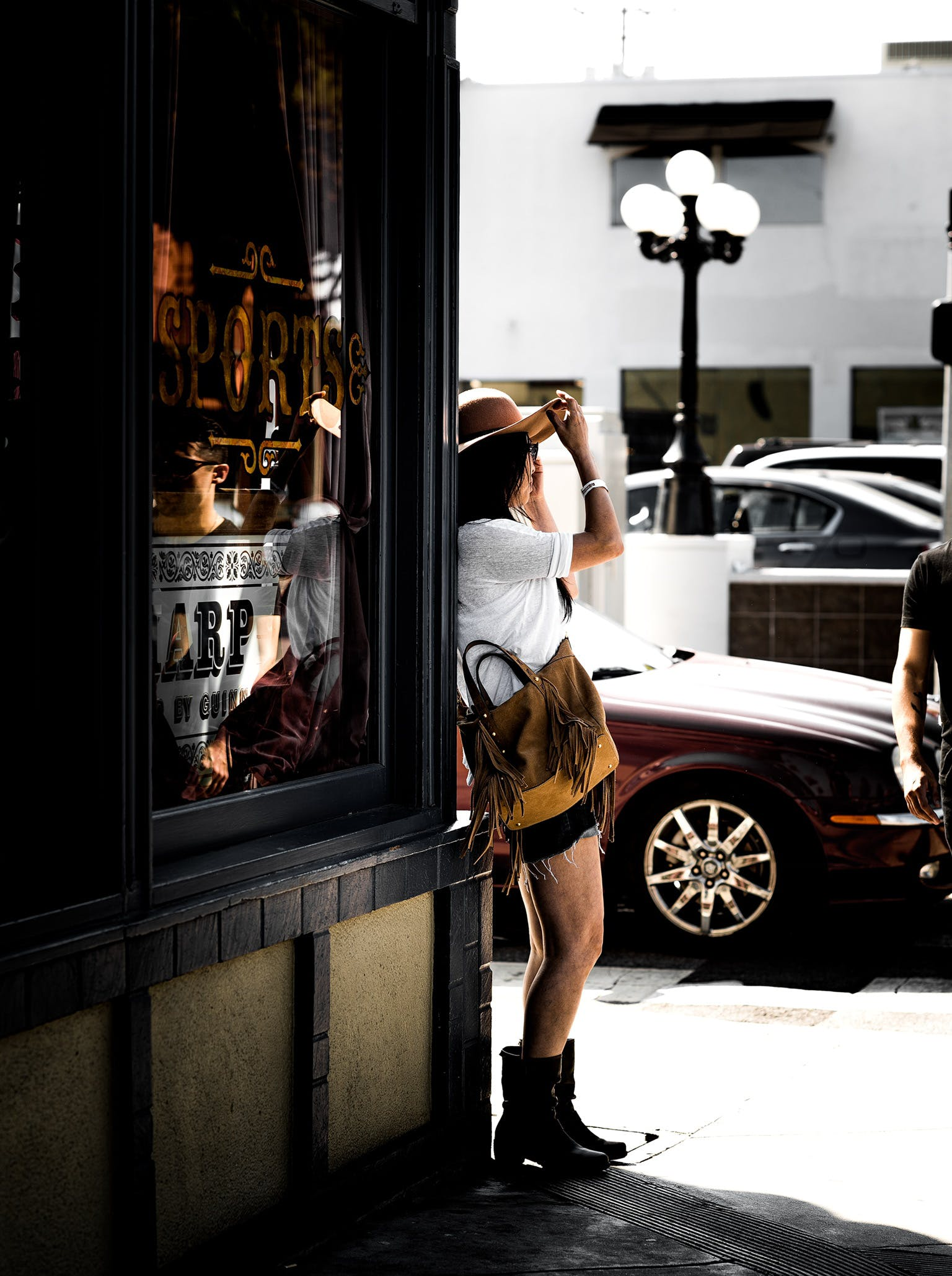 Woman in Brown Sunhat Standing on Sidewalk