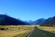 Empty Road Near Mountain Under Blue Skies