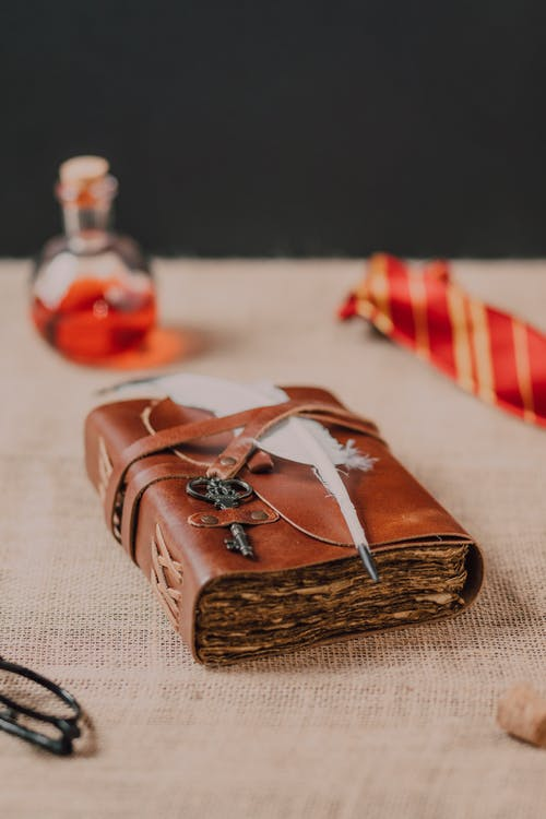 Brown Book and White Feather on Brown Textile