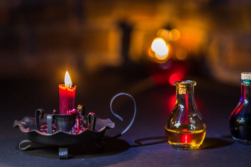 Lighted Candle on Holder Beside a Glass Jar