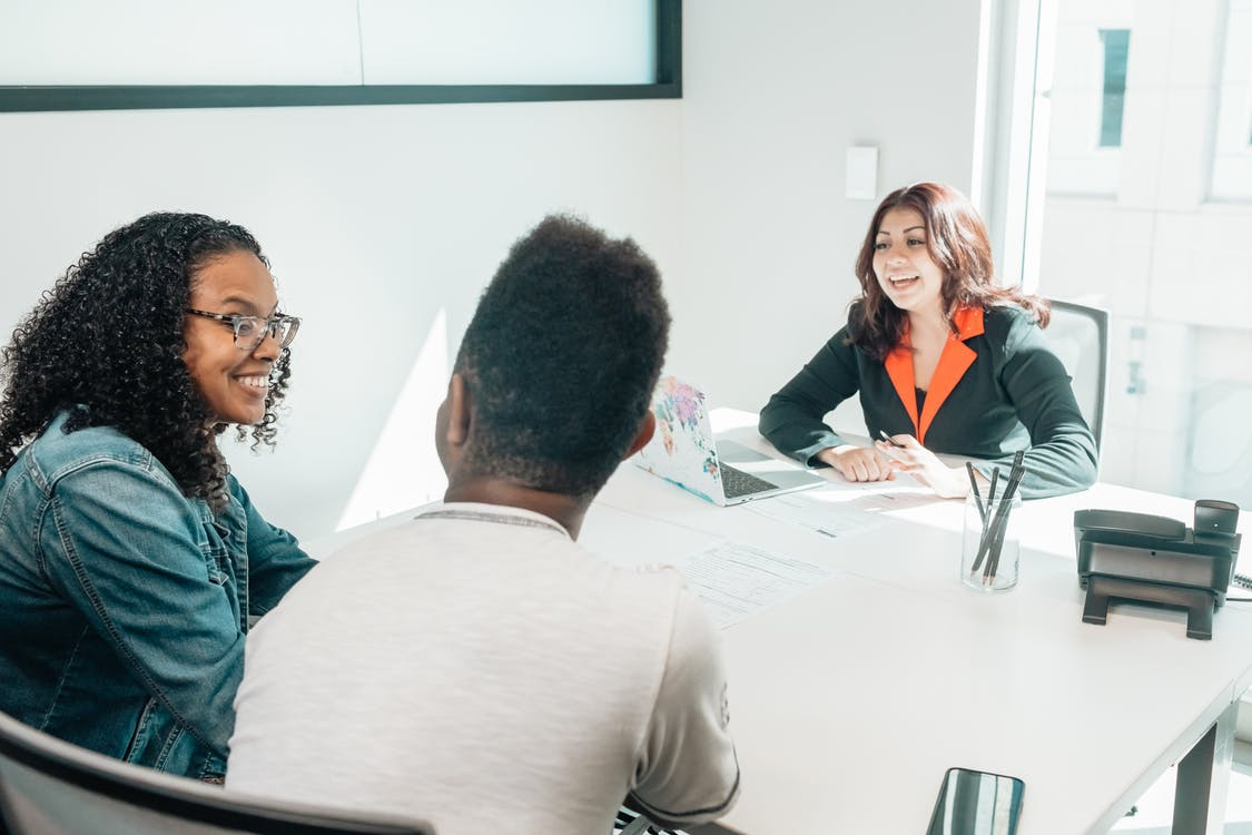 Woman Talking to African American Couple in the Office