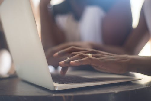 Selective Focus Shot of a Person Typing on a Laptop Keyboard
