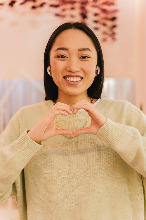 Woman in Beige Sweater and Wireless Earphones Smiling and Showing Heart Shaped Palms