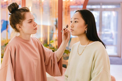 Woman in Oversize T-Shirt Doing Makeup to Woman Sitting in Chair