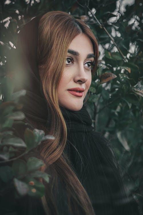 Woman in Black Coat Standing Beside Green Leaves