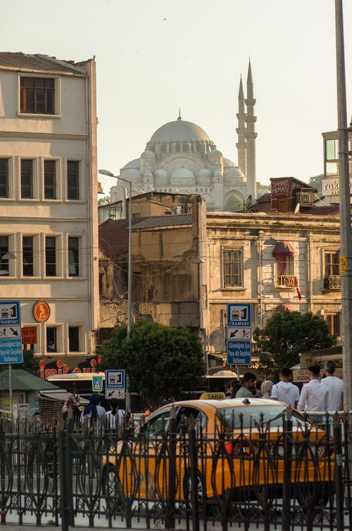 Traditional mosque located behind shabby apartment buildings on crowded street of Islamic city