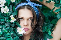 Portrait Photo of Woman in White Top and Blue Polka Dot Headband Near Flowers