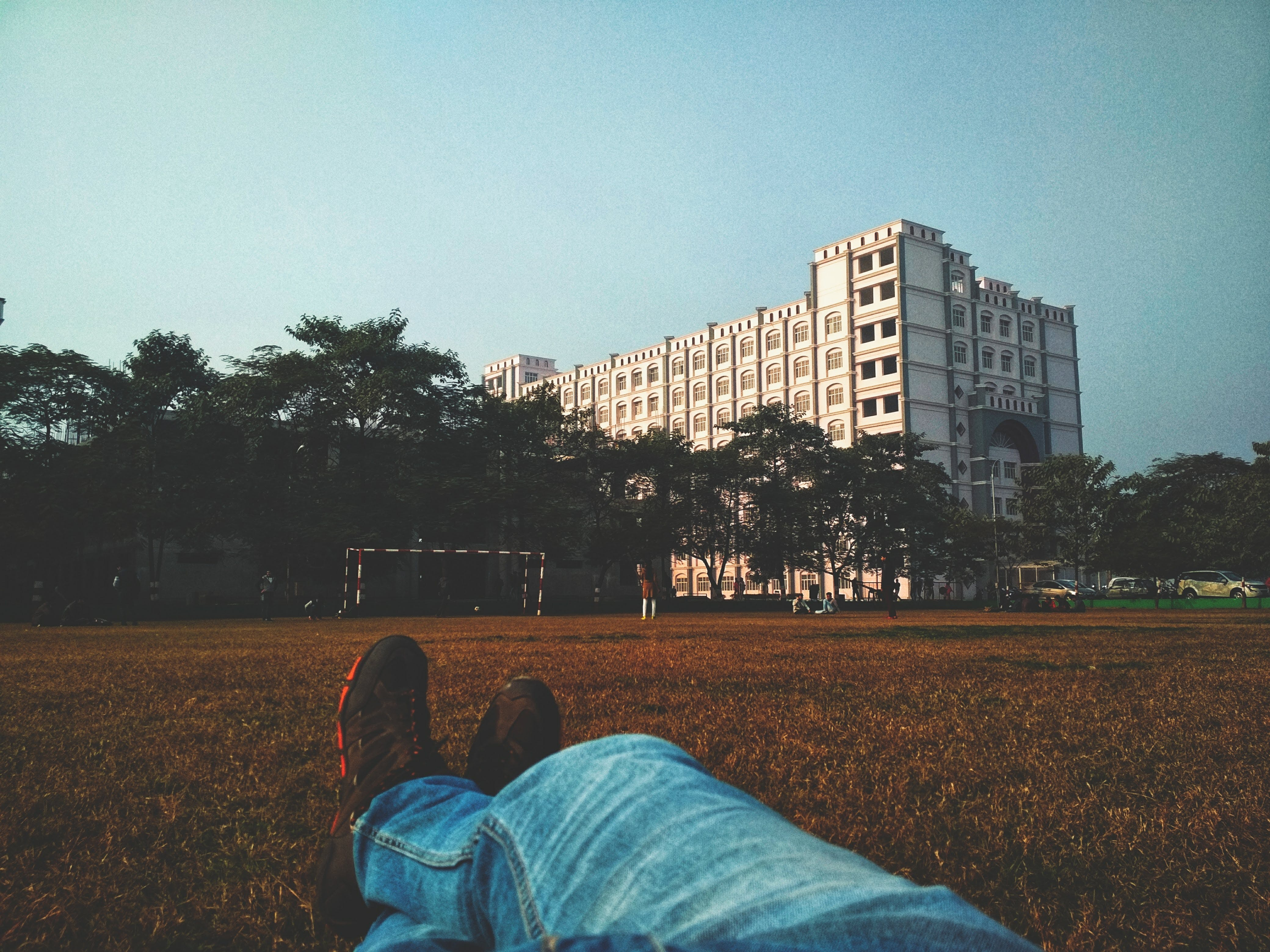 Person in Blue Denim Jean Lying on Brown Grass Field Looking at White Multi-storey Building