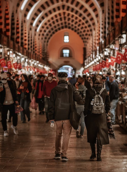Crowd of people walking in dim arched passage decorated with ornaments and flags