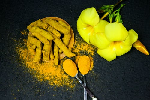 Yellow Elder Flowers Beside a Coated Turmeric