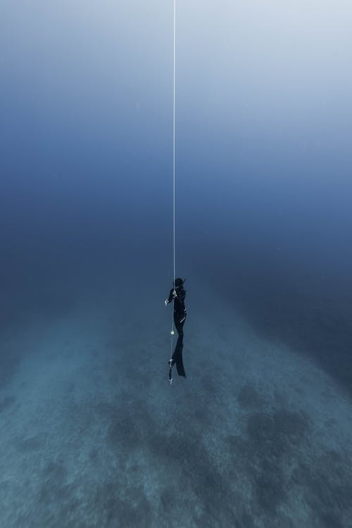 Anonymous diver in flippers and snorkeling equipment holding rope in dark blue seawater