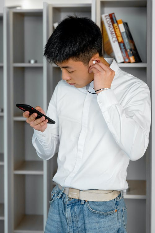 A Young Man Wearing an Earphone Connected to His Cellphone