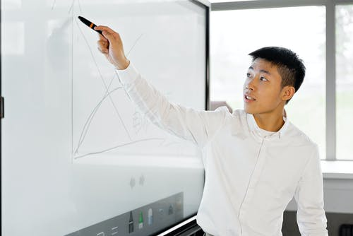 A Man Giving Presentation on the White Screen