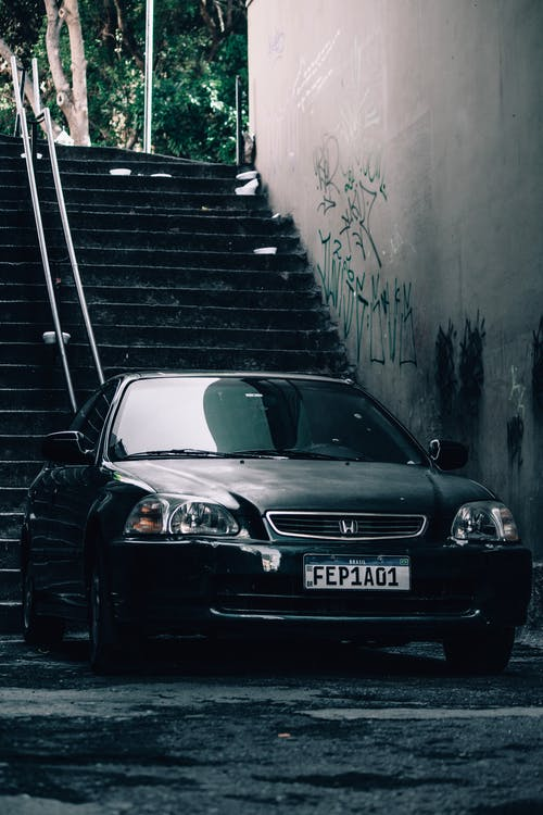 Auto with black shiny polished surface parked near concrete wall with vandal paintings and stairway