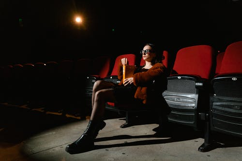 Woman in Brown Jacket Sitting on Red Chair