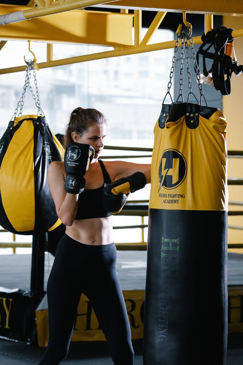 Woman with Boxing Gloves Hitting Punching Bag