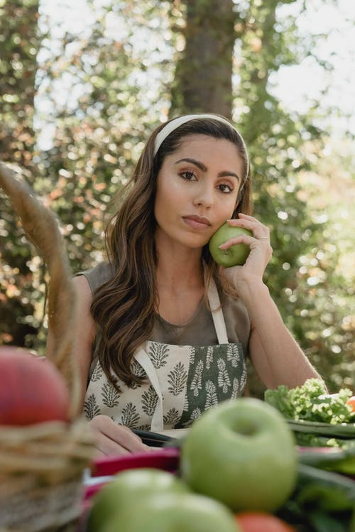 Selective Focus Photo of a Beautiful Woman Holding a Green Apple