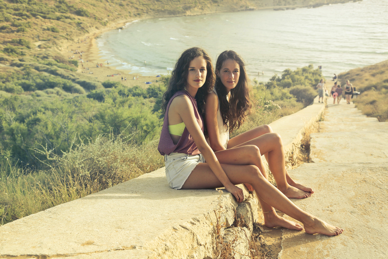 Photo of Teenage Girls Sitting on the Pavement
