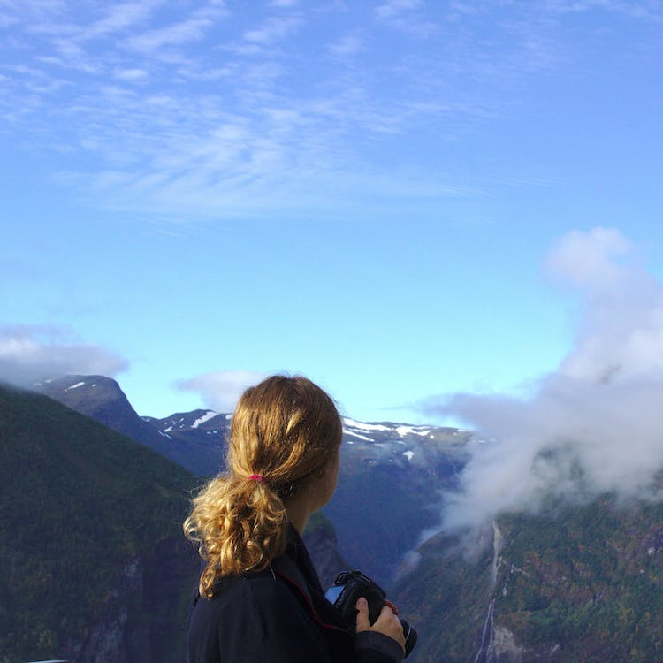 Woman Wearing Black Long Sleeve Shirt Watching on Green and Brown Mountain Under White and Blue Sky during Daytime