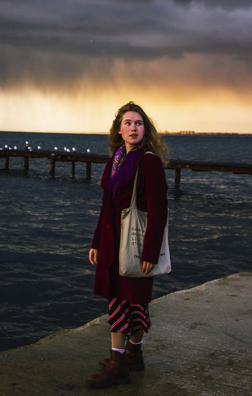 Woman in Red and Black Jacket Standing on Beach during Sunset