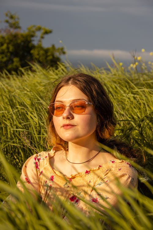 Woman in Yellow and White Floral Shirt Wearing Sunglasses