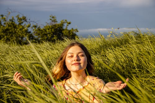 Woman in Yellow and Green Floral Shirt on Green Grass Field