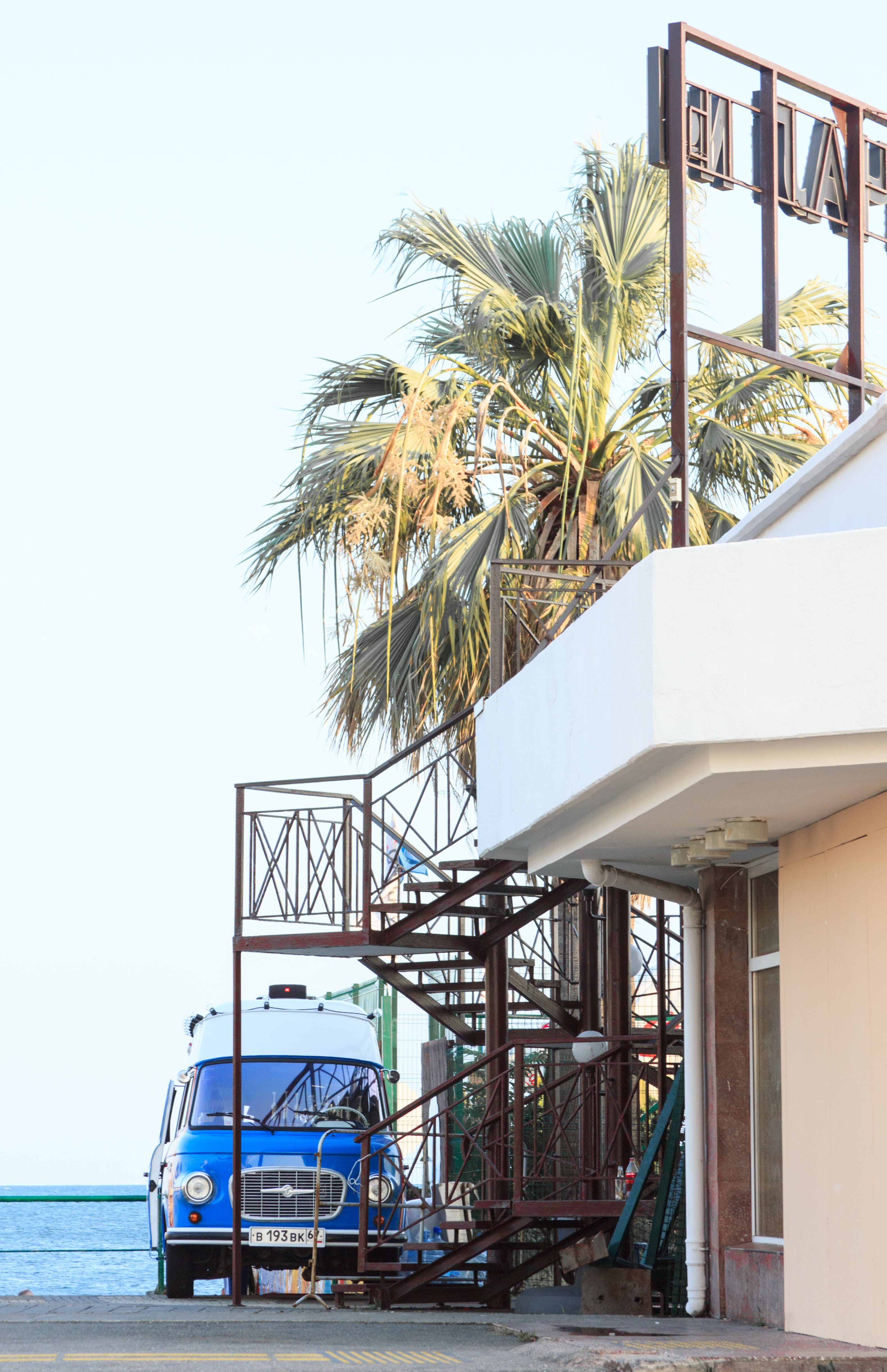 Blue Vehicle Park Near Brown Metal Outdoor Stairs and White Concrete House at Daytime