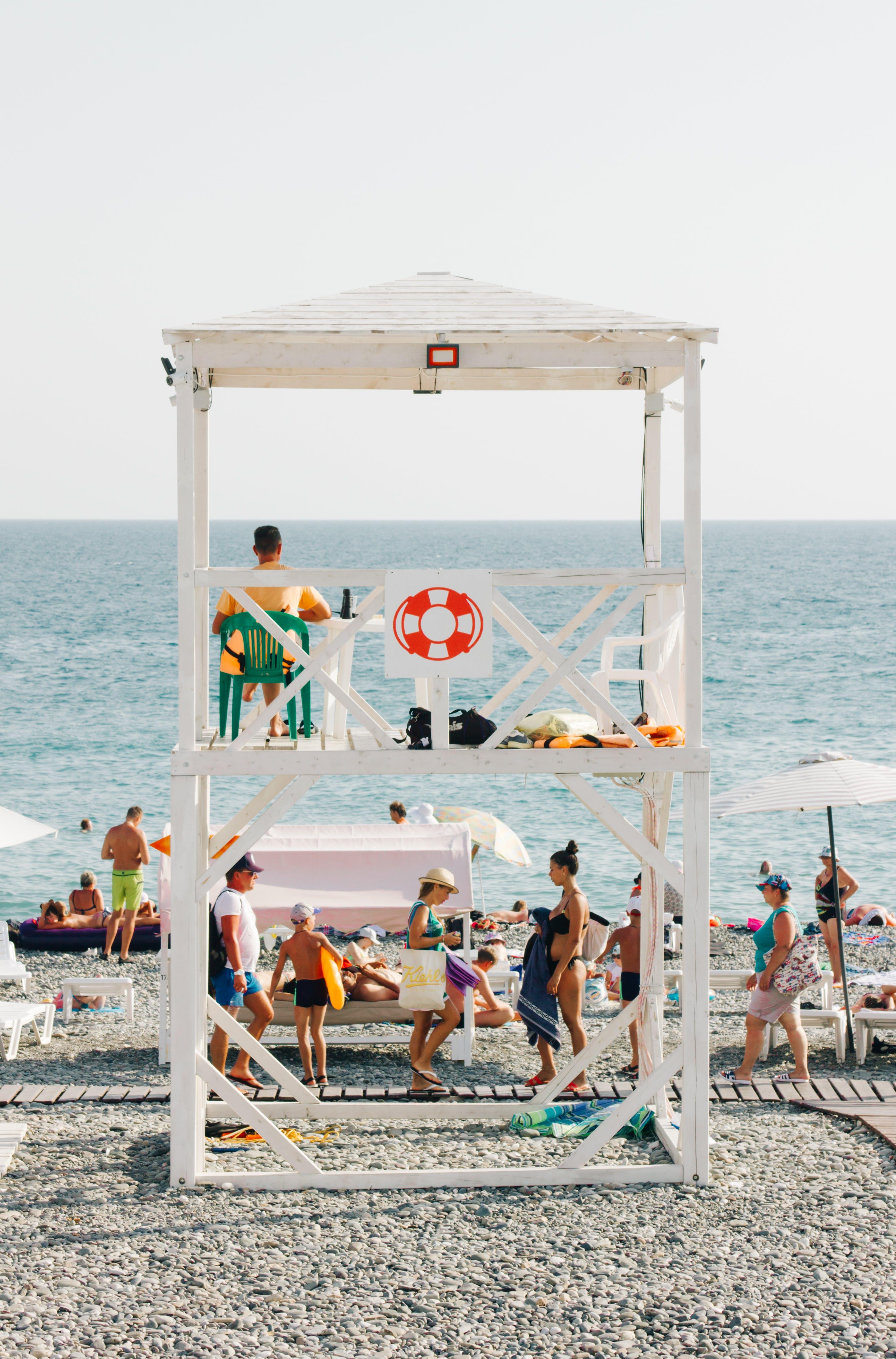 People Near Beach With Lifeguard Gazebo