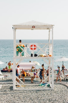 People Near Beach With Lifeguard Gazebo