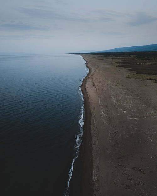 Body of Water Near Brown Sand