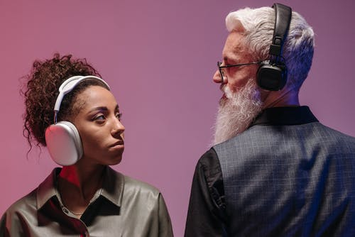 A Man and a Woman Wearing Headphones Looking at Each Other